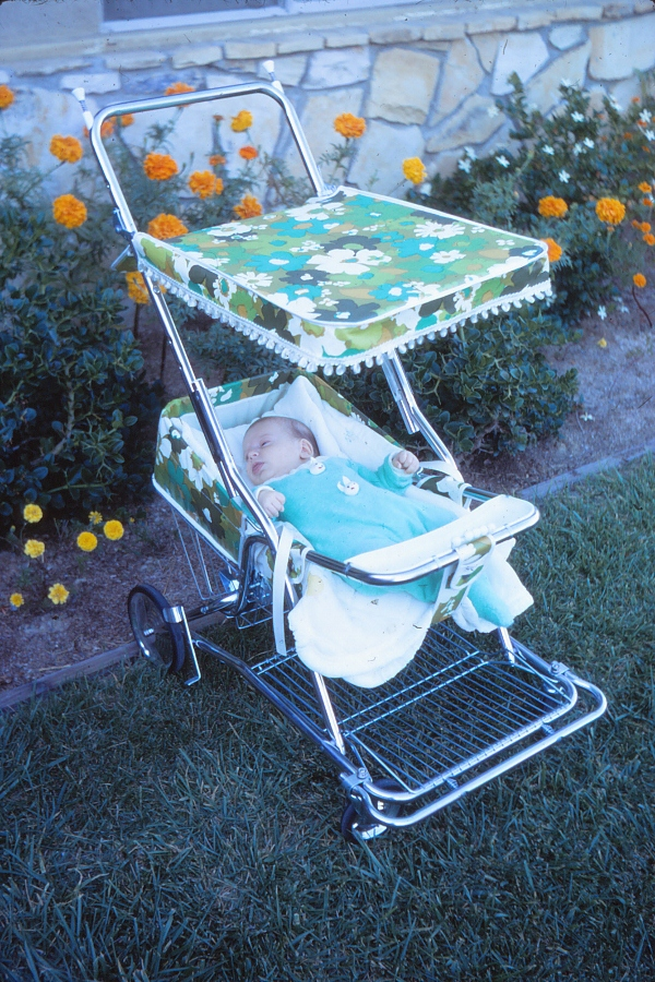 A 1970 Baby Strolee Stroller in avocado green and turquoise floral with white pom pom fringe on the sunshade.