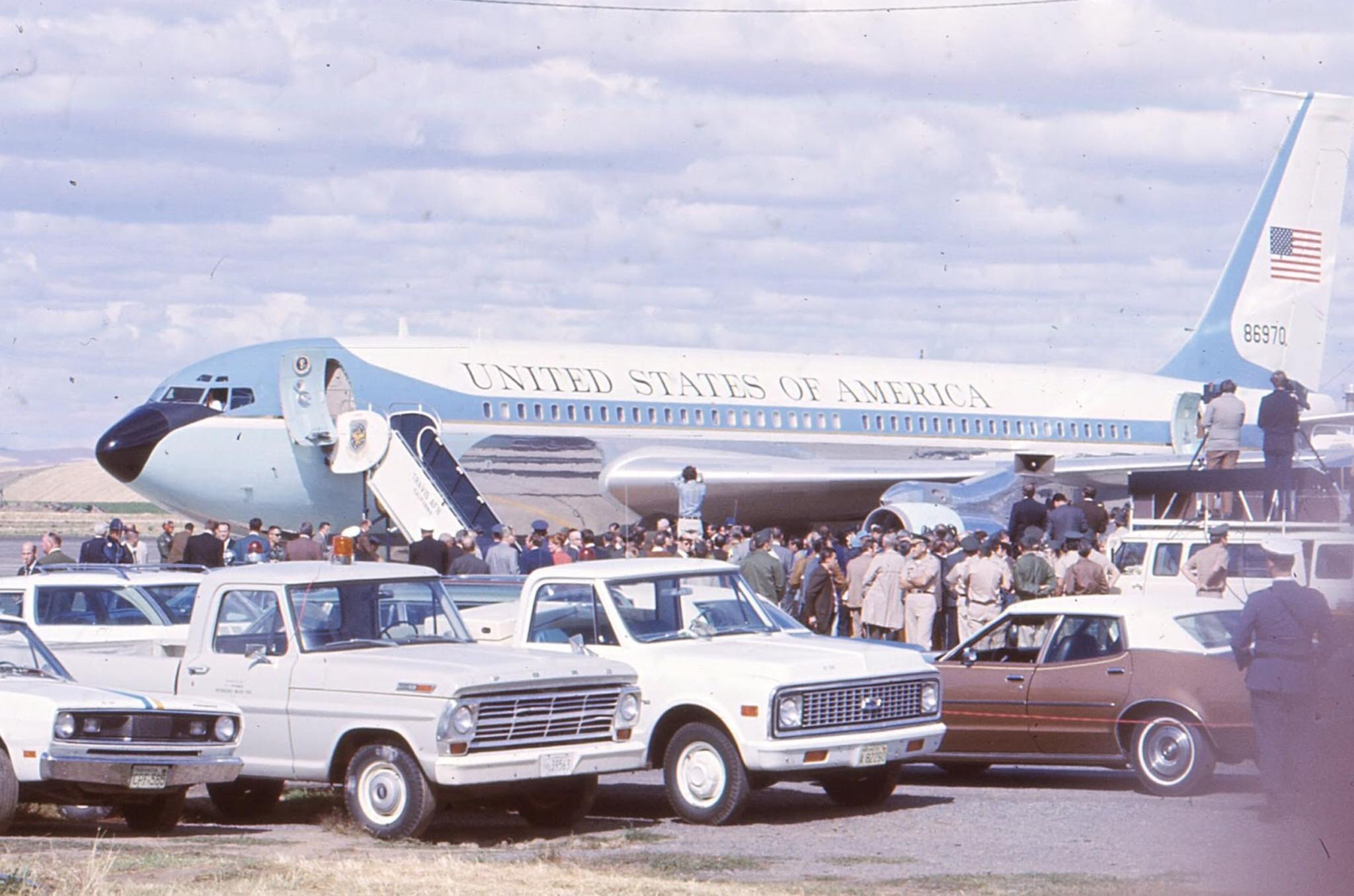 Privately Owned Vehicles parked on the tarmac at an airport in Walla Walla, Washington during the arrival of President Richard Nixon, 1971