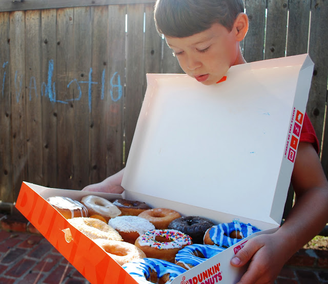 Boy holding box of OKC Thunder Blue Donuts