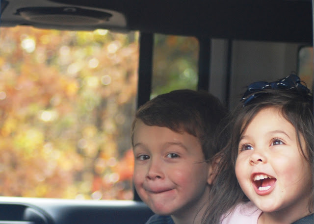 Children traveling in a car with fall colors in the background.